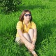Young woman sitting on grass — Foto de Stock