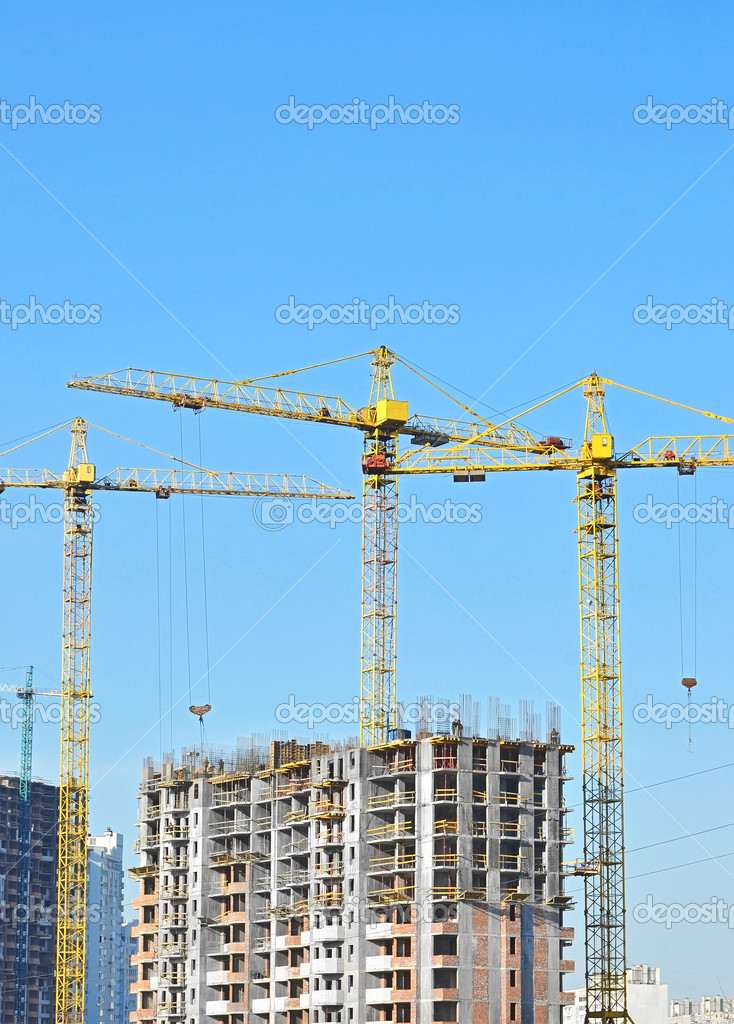 Building crane and building under construction against blue sky — Stock Photo #9912630