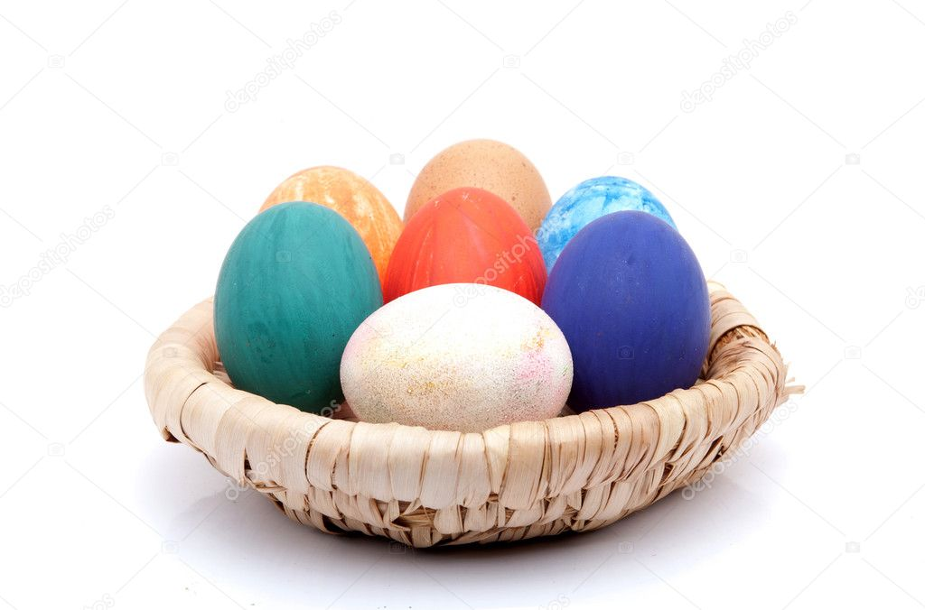 Colored Easter eggs in a wicker plate on a white background — Stock Photo #9801337