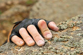 Rockclimber's hand on granite rock in gloves — Stock Photo