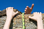 Rock climber reaching for helping-hand partner. — Stock Photo
