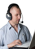 A young man with headphones and a laptop — Stockfoto