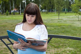 Portrait of nice young smiling woman with book — Stock Photo