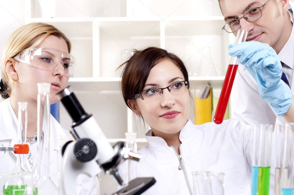 Chemists working with a team looking at the tube — Stock Photo #10122111