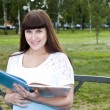Beautiful pregnant woman read book in the park — Stock Photo