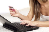 Young woman holding credit card and using laptop — Stock Photo