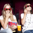 Two beautiful girls watching a movie at the cinema — Stock Photo #8824422