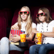 Two beautiful girls watching a movie at the cinema - Stock Photo