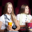 Two beautiful girls watching a movie at the cinema — Stock Photo #9073122