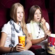 Two beautiful girls watching a movie at the cinema — Stock Photo #9155399