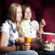 Two beautiful girls watching a movie at the cinema — Foto de Stock