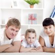 Portrait of happy family lying together, hugging and happy — Stock Photo