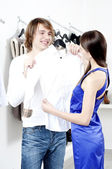 Cute man and the woman in shop choose clothes — Stockfoto