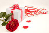 Red rose, two hearts and white gift on a white background — Stock Photo