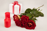 Red roses, two candles and white gift on a white background — Stock Photo