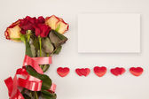 Bouquet of roses, white card and a line of hearts on a white background — Stock Photo