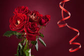 Bouquet of red roses with a serpentine on a red background — Stock Photo