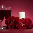 Bouquet of red roses, two glasses of wine and a candle on red background — Stock Photo #8896297