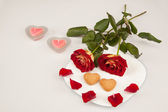 Two red roses and two hearts on a white plate with two candles — Stock Photo