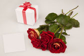 Red roses, white gift and card on a white background — Stock Photo
