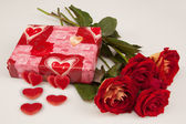 Red roses and gift for St.Valentine's Day on a white background — Stock Photo