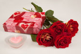 Red roses, candle and gift for St.Valentine's Day on a white backgroun — Stock Photo