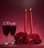 Bouquet of red roses, two glasses of wine and two candles on red background — Stock Photo