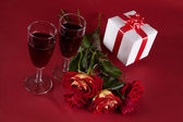 Bouquet of red roses, white gift and two glasses of wine on a red backgroun — Stock Photo