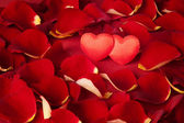 Two hearts in rose petals on a red background — Stock Photo