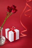 Bouquet of red roses and white gift on a red background — Stock Photo