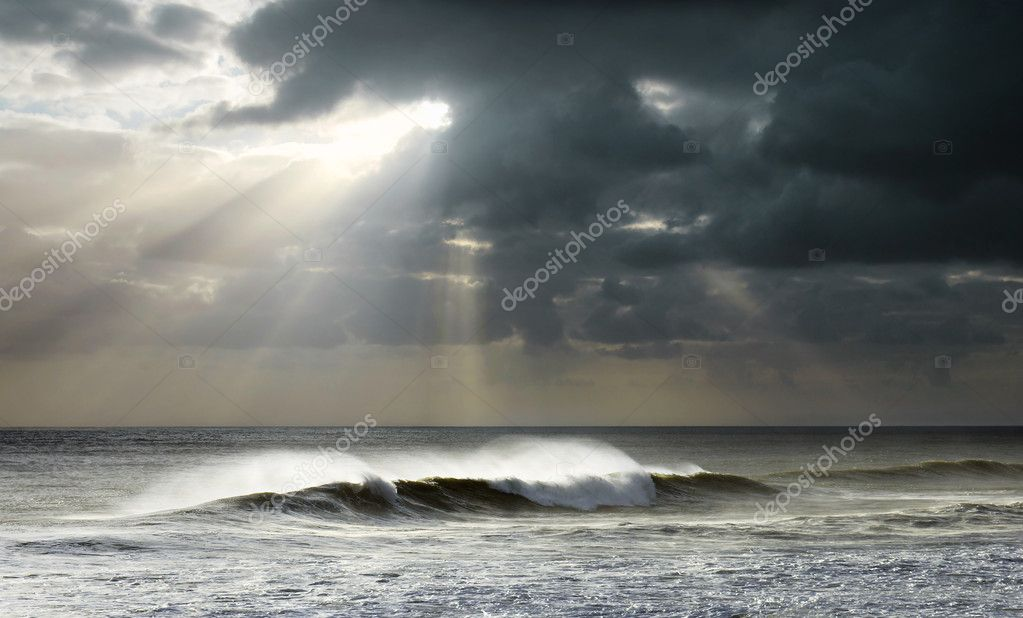 Beautiful seascape with bright sun rays and dark clouds over a wavy sea — Stock Photo #8526013