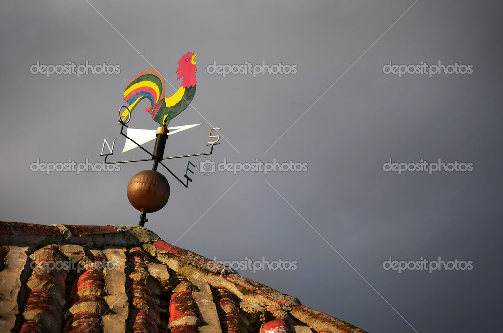 Colorful weather vane with cock figure over cloudy sky — Stock Photo #8526078
