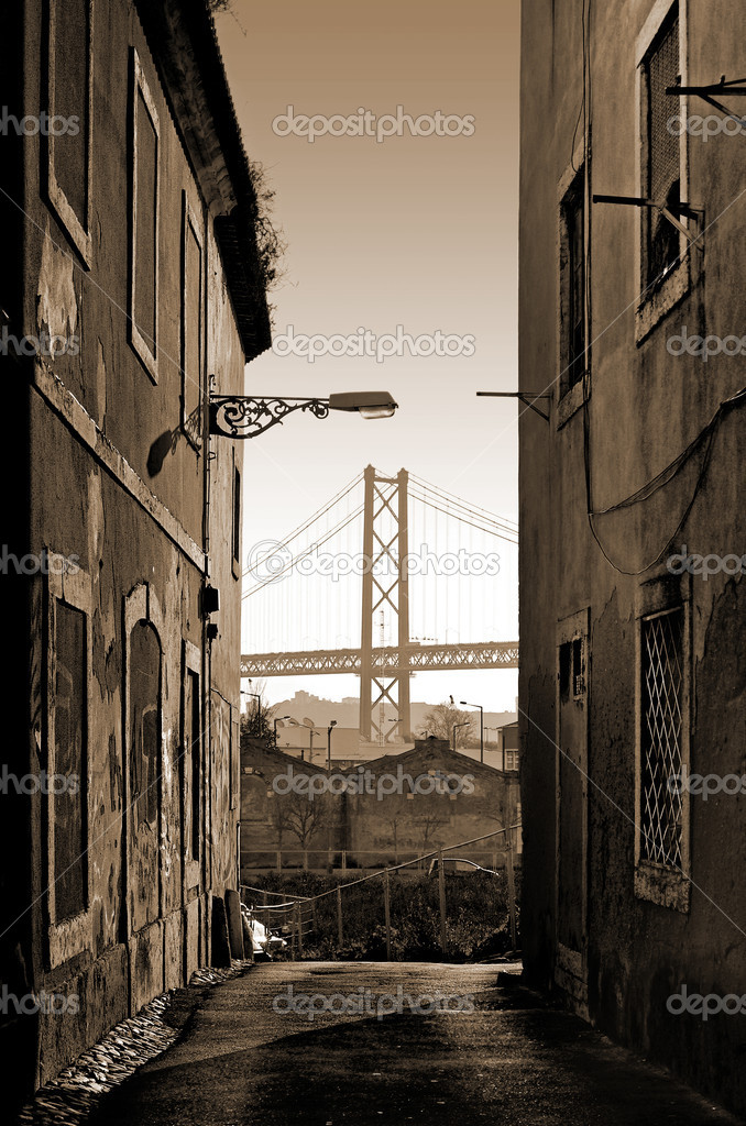 Narrow old street with abandoned buildings and view to the bridge 25 April in Lisbon, Portugal — Stock Photo #8526123
