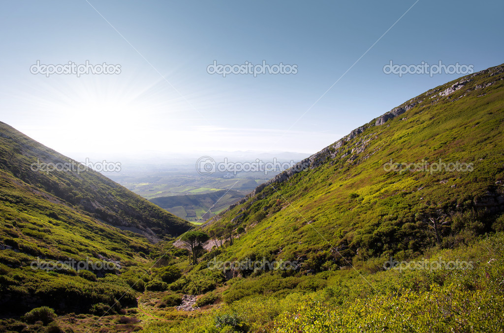 Landscape of green hills with blue sky and bright sunshine  Stock Photo #8935612