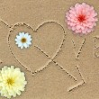 Love word with love symbol and flowers on sand — Stock Photo