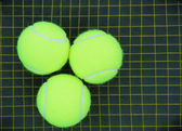 Three tennis ball on a racket strings in the background — Zdjęcie stockowe