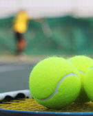 Tennis balls on racket and a person in background — Stockfoto