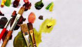 Paint brushes and different paint pigments — Stock Photo
