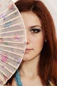 Garota ruiva sexy jovem com ventilador — Fotografia Stock