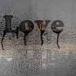 Love , text on the condensation window, after rain — Stock Photo