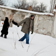 Stock Photo: Homeless couple walking in the snow holding hands
