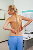 Topless female patient back pain — Stock Photo