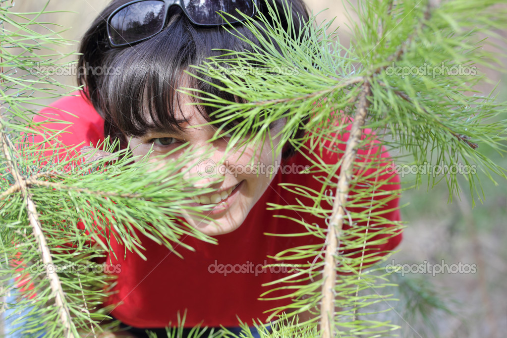 Beautiful laughing girl hiding behind a small pine tree — Stock Photo #10240825