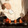 A young man holds a Chinese tea ceremony - Stock Photo