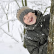 Smiling boy in winter forest — Stockfoto