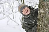 Smiling boy in winter forest — Stock Photo