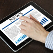 Touch screen device with business news — Stock Photo