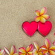 Stock Photo: Frangipani /plumeria flower frame, with two red hearts on sand