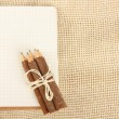 Notebook and pencils on burlap — Stock Photo