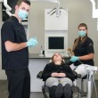 Dentist with nurse and patient — Stock Photo